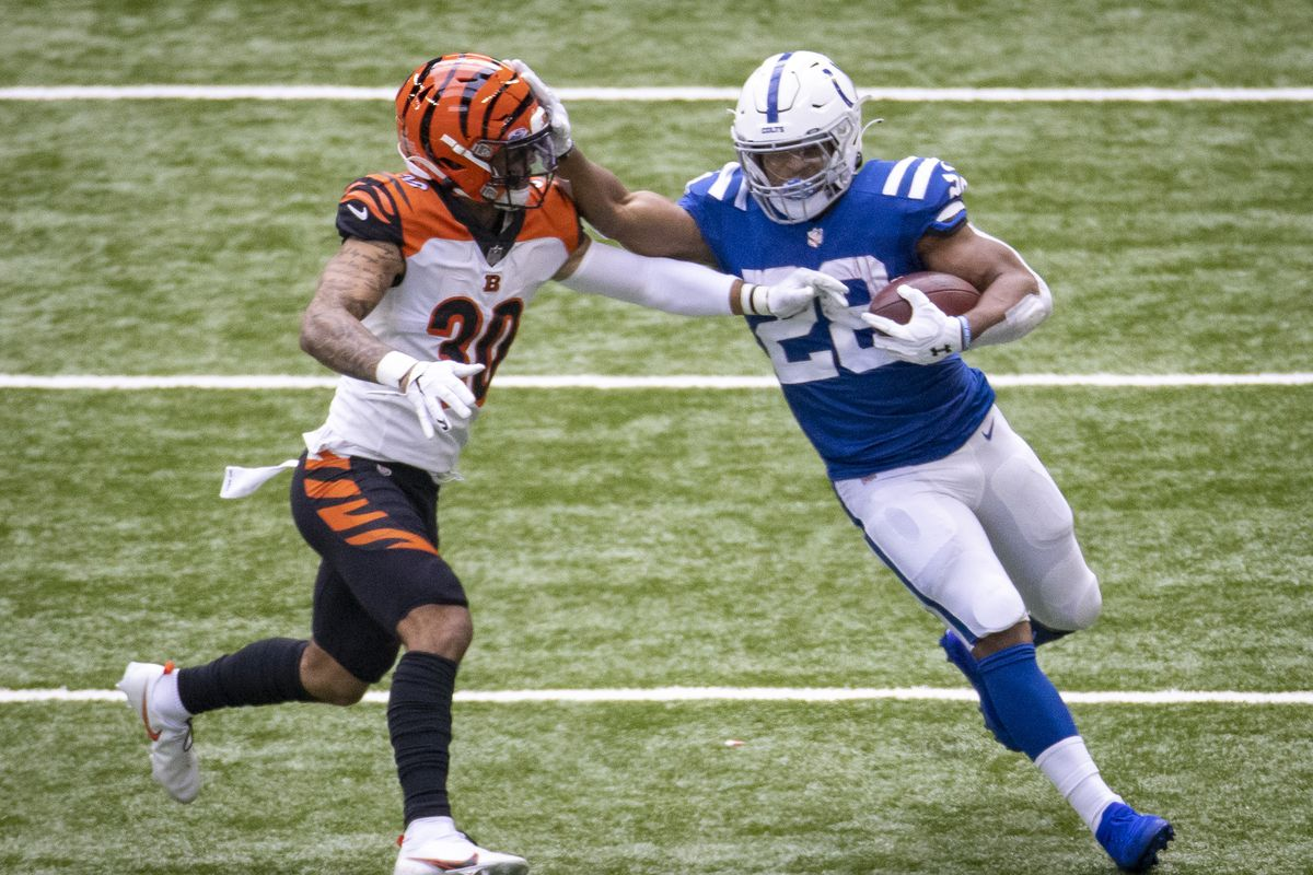 Jonathan Taylor #28 of the Indianapolis Colts stiff arms Jessie Bates #30 of the Cincinnati Bengals as he runs down the field during the third quarter of the game at Lucas Oil Stadium on October 18, 2020 in Indianapolis, Indiana.