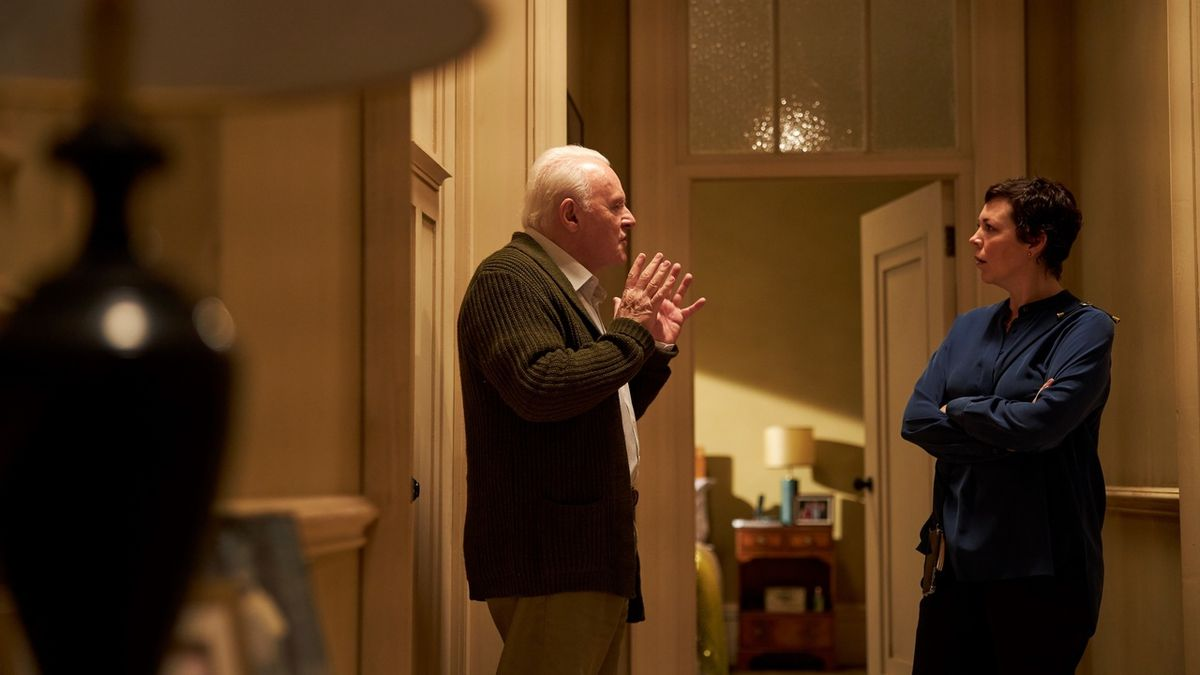 An elderly father and middle-aged daughter stand in a hallway. She listens as he gesticulates.