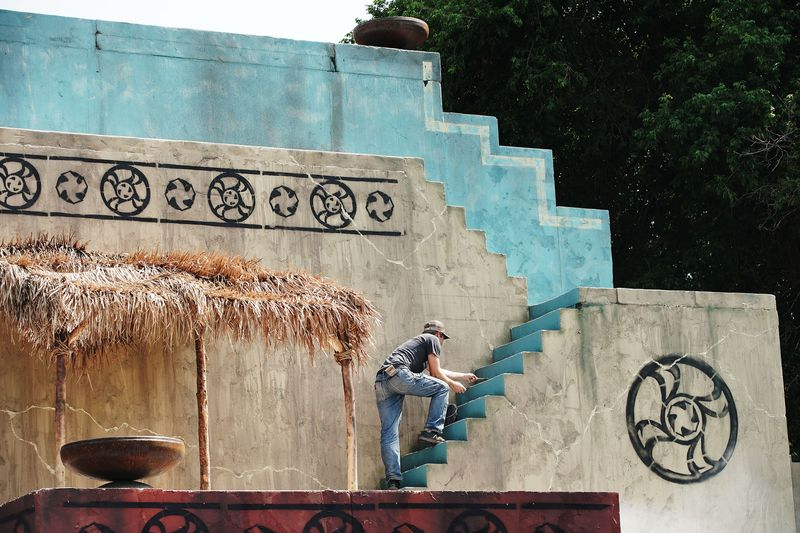 A crew member paints the styrofoam set during production of the fourth season of Book of Mormon videos.