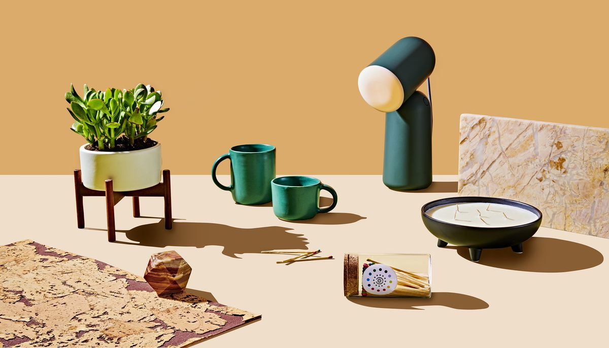 Products on a table which are part of the Curbed Holiday Gift Guide 2019. There is a table lamp, green mugs, a jar of colorful matches, a jar candle, and a planter with a green plant. The products are sitting on a flat surface.