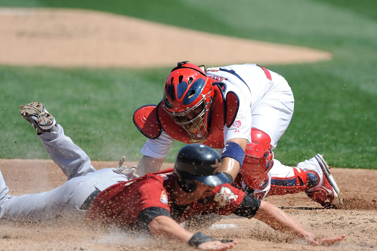 ST. LOUIS, MO - AUGUST 23: Scott Moore #46 of the Houston Astros slides safely past Yadier Molina #4 of the St. Louis Cardinals at Busch Stadium on August 23, 2012 in St. Louis, Missouri. (Photo by Jeff Curry/Getty Images)