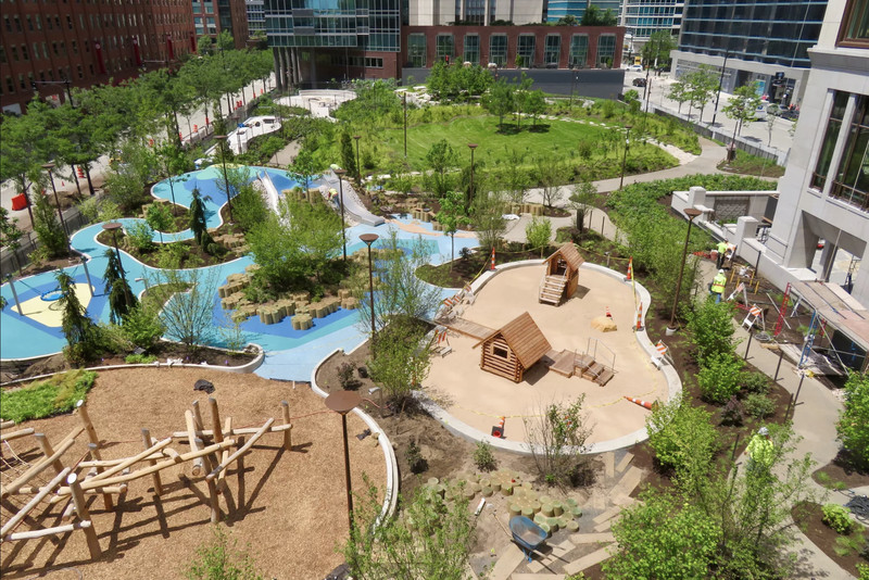 An overhead view of a park surrounded by high-rise buildings. There's a playground with slides, play huts, and a climbing forest plus two concrete dog runs and a circular green lawn with raised edges.
