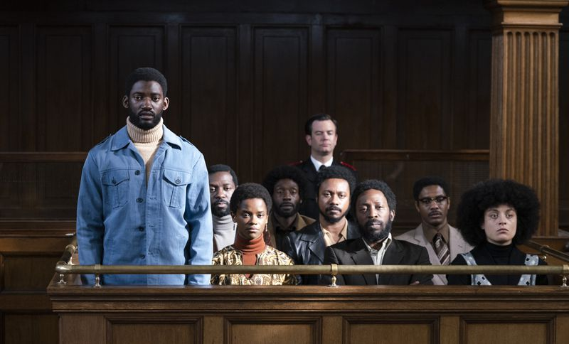 A group of people sit in a box in a courtroom.