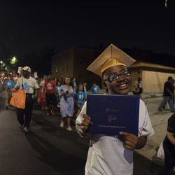 Aaliyah Borsey, 15, stands with her diploma on 83rd Street. Borsey had just graduated from Ryder Elementary. | Colin Boyle/Chicago Sun-Times