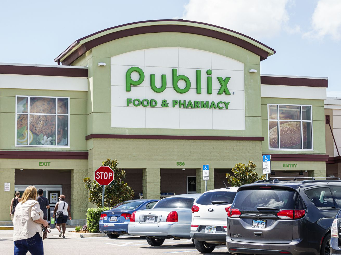 The exterior of a Publix supermarket in Florida, Lake Placid, with customers walking out of their cars and toward the store.