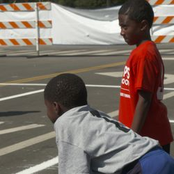 During one of Hoops in the Hood's tournament games two young boys pause to catch their breath.