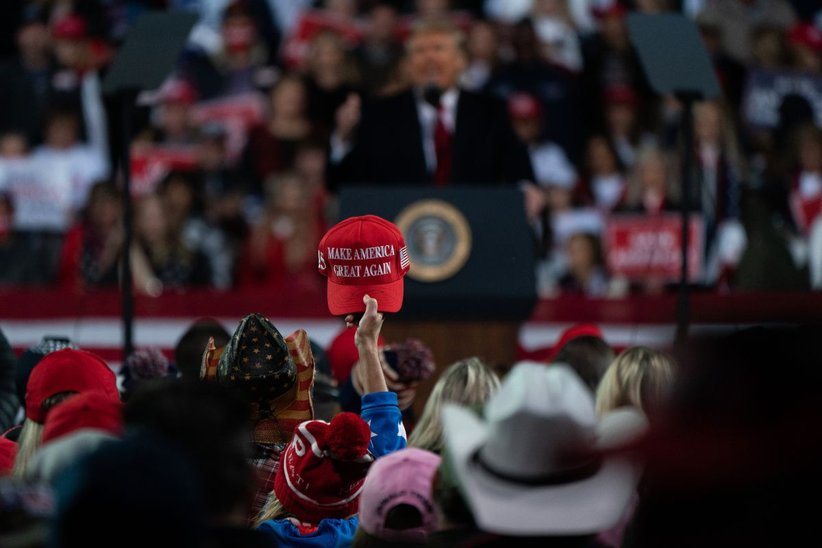A person holds up a MAGA hat at a Trump rally.