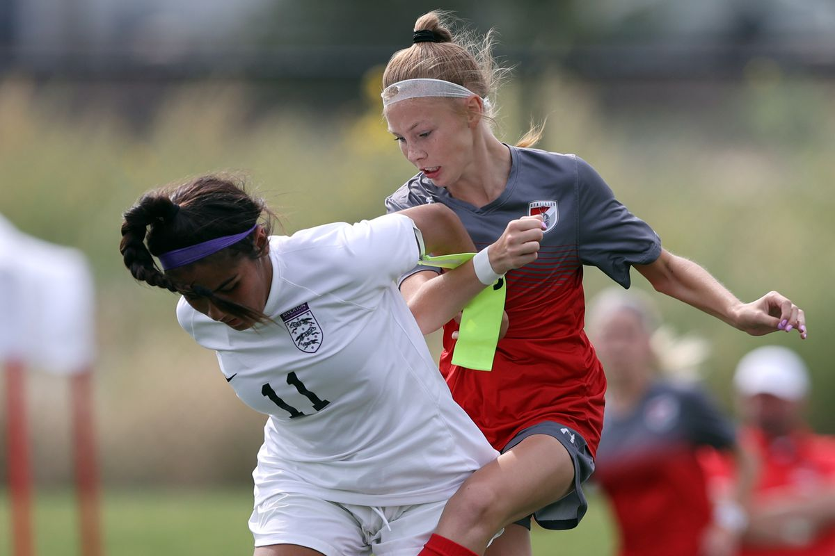 Riverton's Mariana Regla and Mountain Ridge's Jocelyn Wright battle for the ball as they play in a high school soccer game.