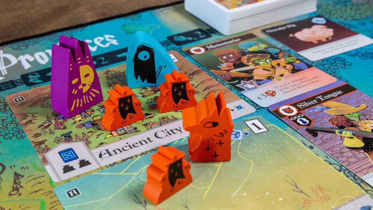 A selection of pawns from Oath, including the wooden Chancellor. The art on the cards and playing mat is bright and cheerful, with fantasy creatures and woodland creatures intermixed.