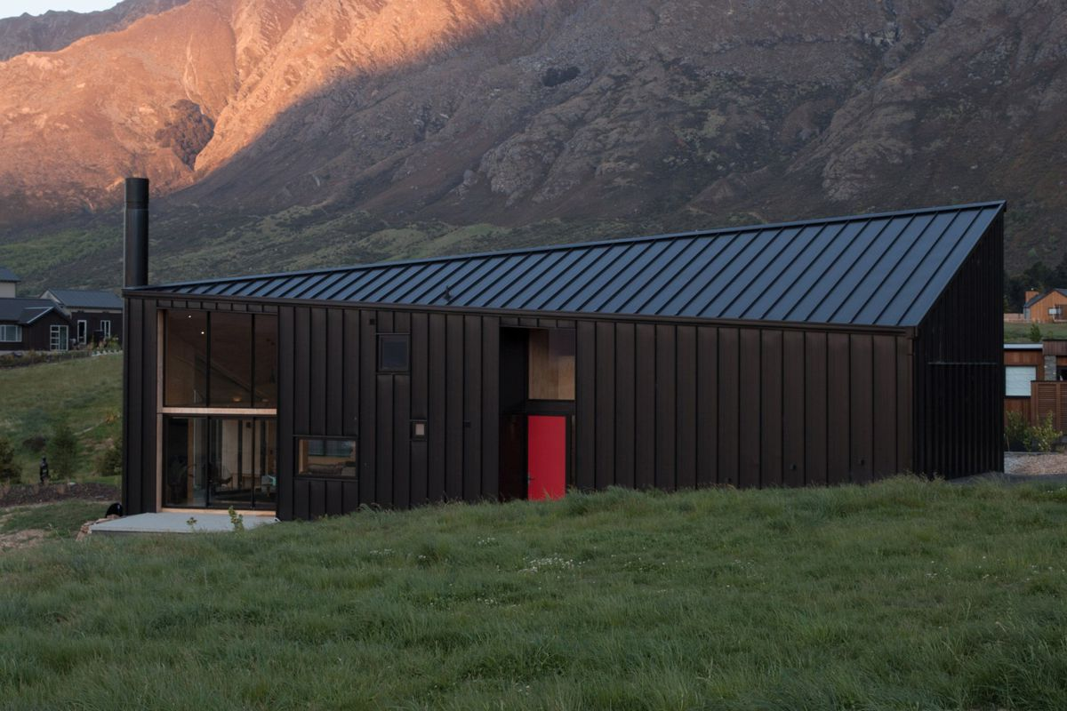 Black-clad cabin with asymmetrical roofline in mountain setting.
