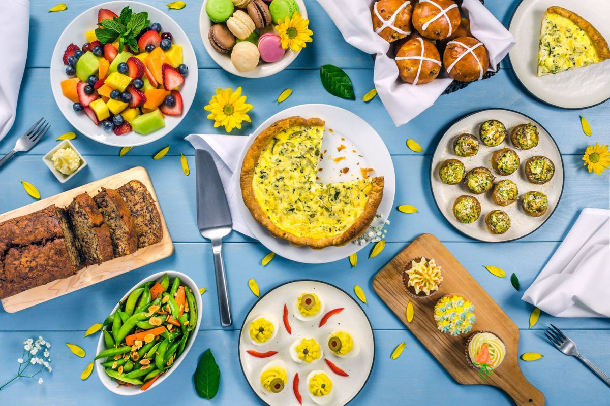 A blue table with quiche, deviled eggs, stuffed mushrooms, loaves, and fruit salad from Elephant's Deli
