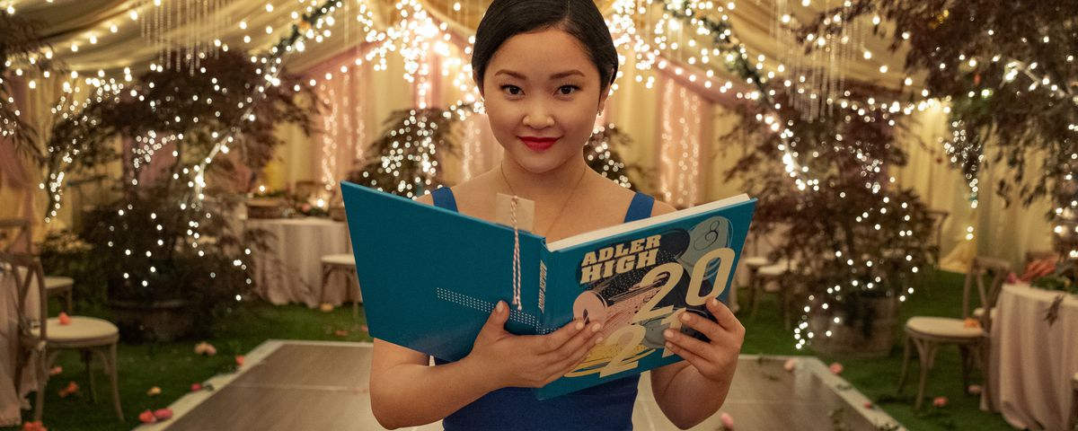 lara jean in a bridesmaids dress holding her yearbook