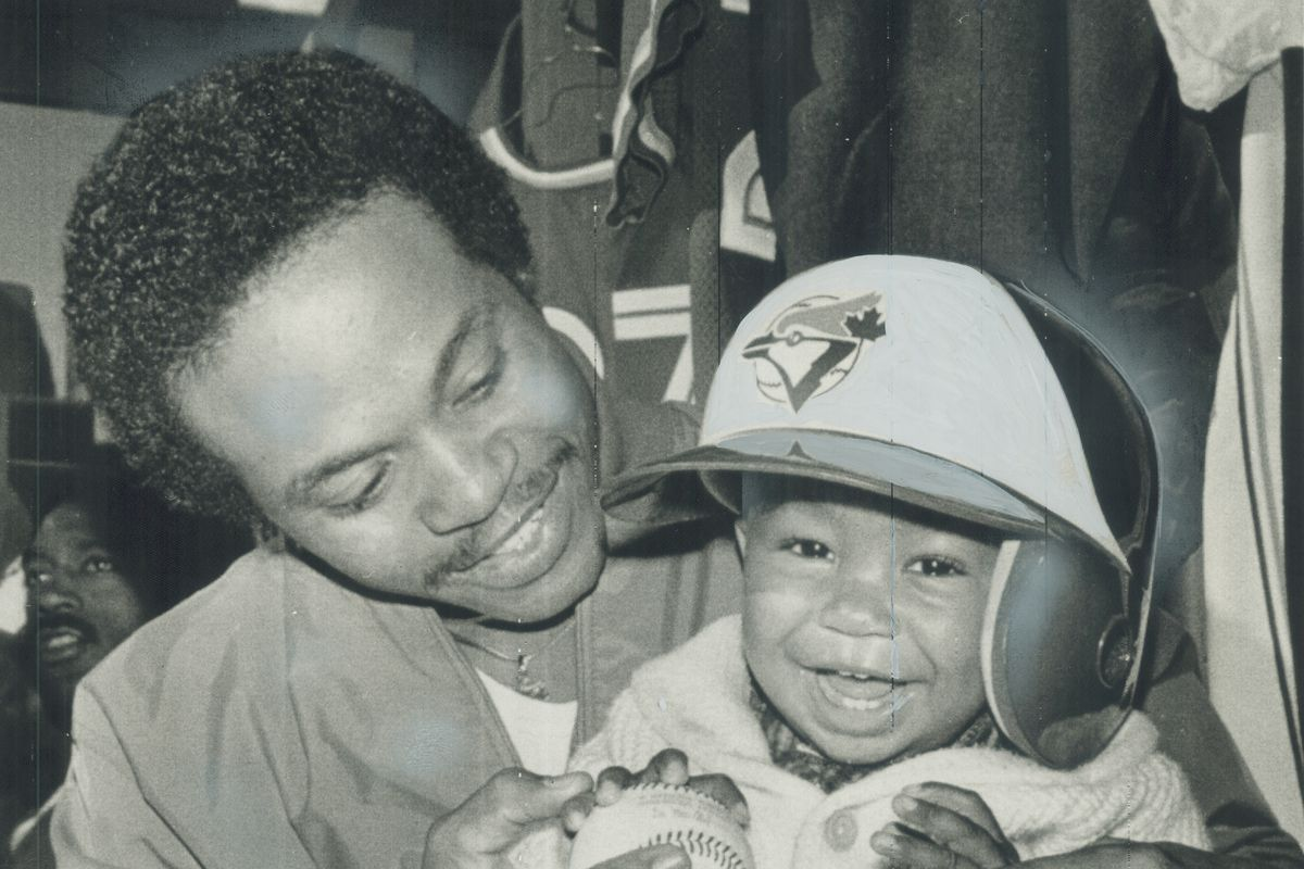 Littlest blue Jay: Fourteen-month-old Joshua Barfield gets the feel of a baseball from his father, J