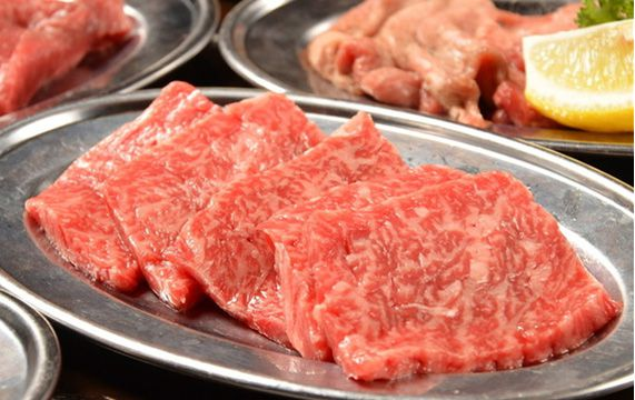 Six to seven slices of raw meat sit on a metal serving dish with other dishes of meat blurred in the background