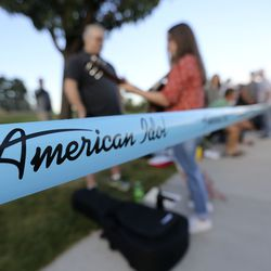 """Tifanee Hatch plays the guitar and sings while waiting in line for """"American Idol"""" auditions outside of the Northwest Community Center in Salt Lake City on Thursday, Aug. 29, 2019."""