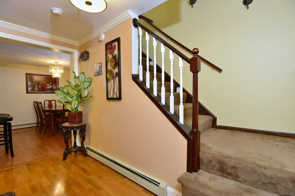 The entry of a house, with a stairwell off a hallway leading to a dining room.
