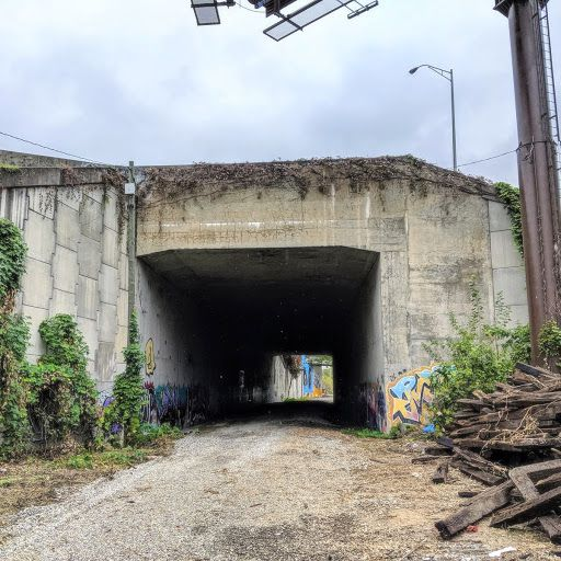 A tunnel with graffiti beneath a huge highway.