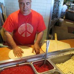 John Arena makes a pizza.