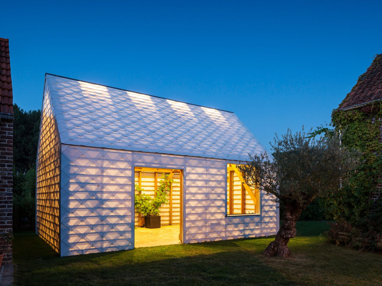 Gabled cabin made of translucent shingles glows at night.