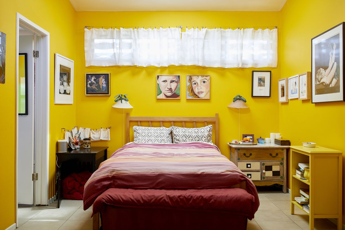 A bedroom with yellow painted walls. On the walls  are multiple framed works of art. In the center of the room is a bed with colorful red patterned bed linens. There are multiple tables around the room.