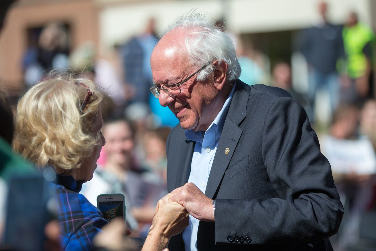 Bernie Sanders shaking hands with a supporter at a rally.