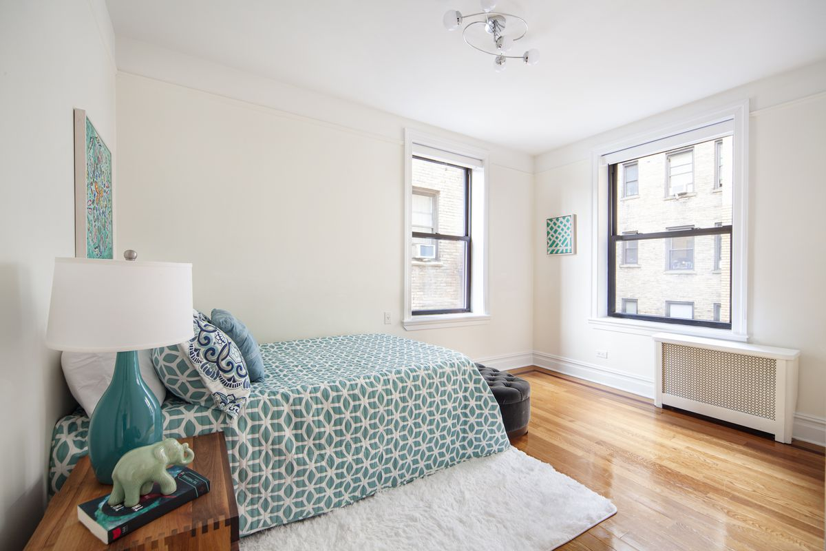 A bedroom with a small bed, hardwood floors, two windows, beige walls, and a white rug.
