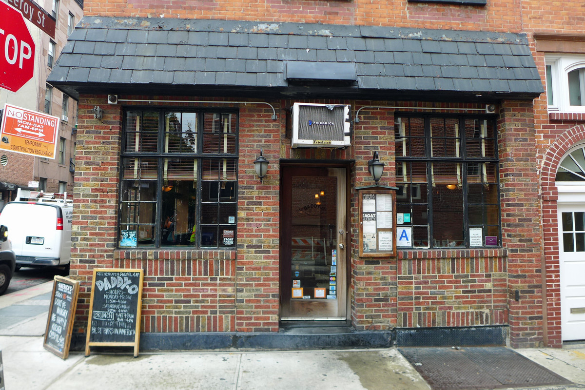 The exterior of a red brick building with two large windows on either side and a chalkboard lying out front by the entrance
