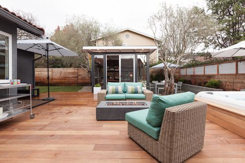 An outdoor patio with chairs and a fire pit. There is a grey umbrella. The deck floor is wood.