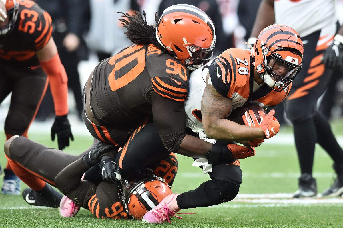 Cleveland Browns defensive end Chad Thomas and defensive tackle Brandin Bryant tackles Cincinnati Bengals running back Joe Mixon during the second half at FirstEnergy Stadium