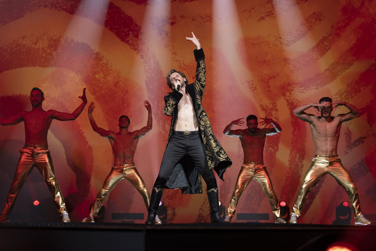 stevens is shirtless in front of four back-up dancers