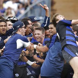 Game MVP Jonny Linehan is surrounded by teammates as they celebrate as BYU defeats Cal 27-24 in rugby on a drop as time expires to win the Varsity Cup national championship Saturday, May 4, 2013, in Provo.