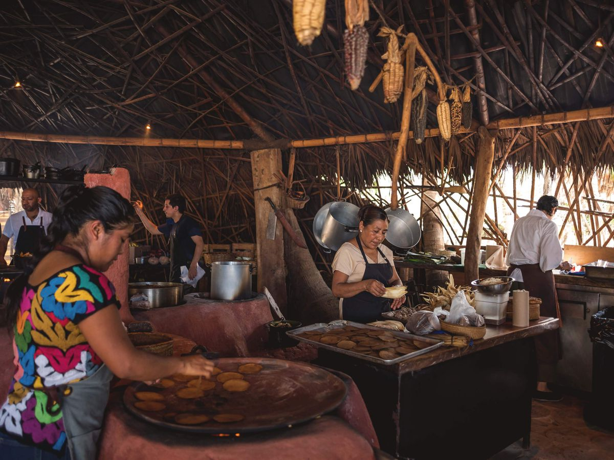 Two women stand in the foreground preparing tortillas and cooking them on a griddle, with several other chefs at work in the background in an open air kitchen with a thatched roof.