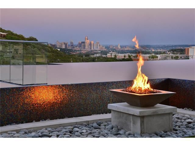 A deck with a firepit on a pedestal and a killer view of downtown Austin in the background