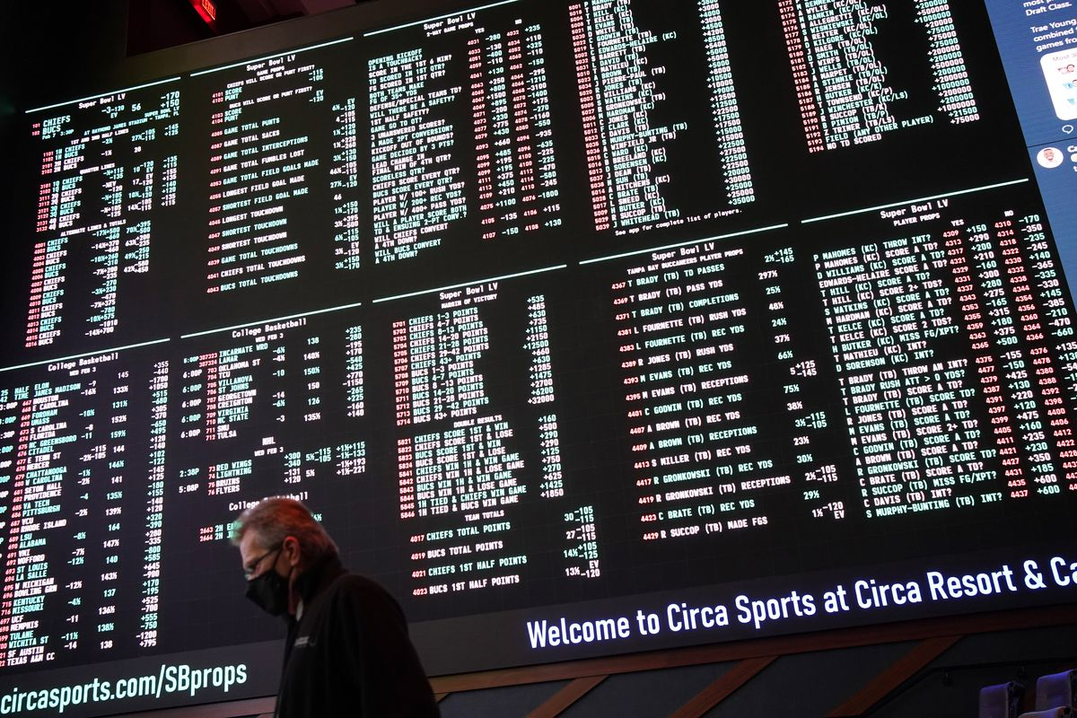 A man walks by as betting odds for NFL football's Super Bowl 55 are displayed on monitors at the Circa resort and casino sports book in Las Vegas in February.