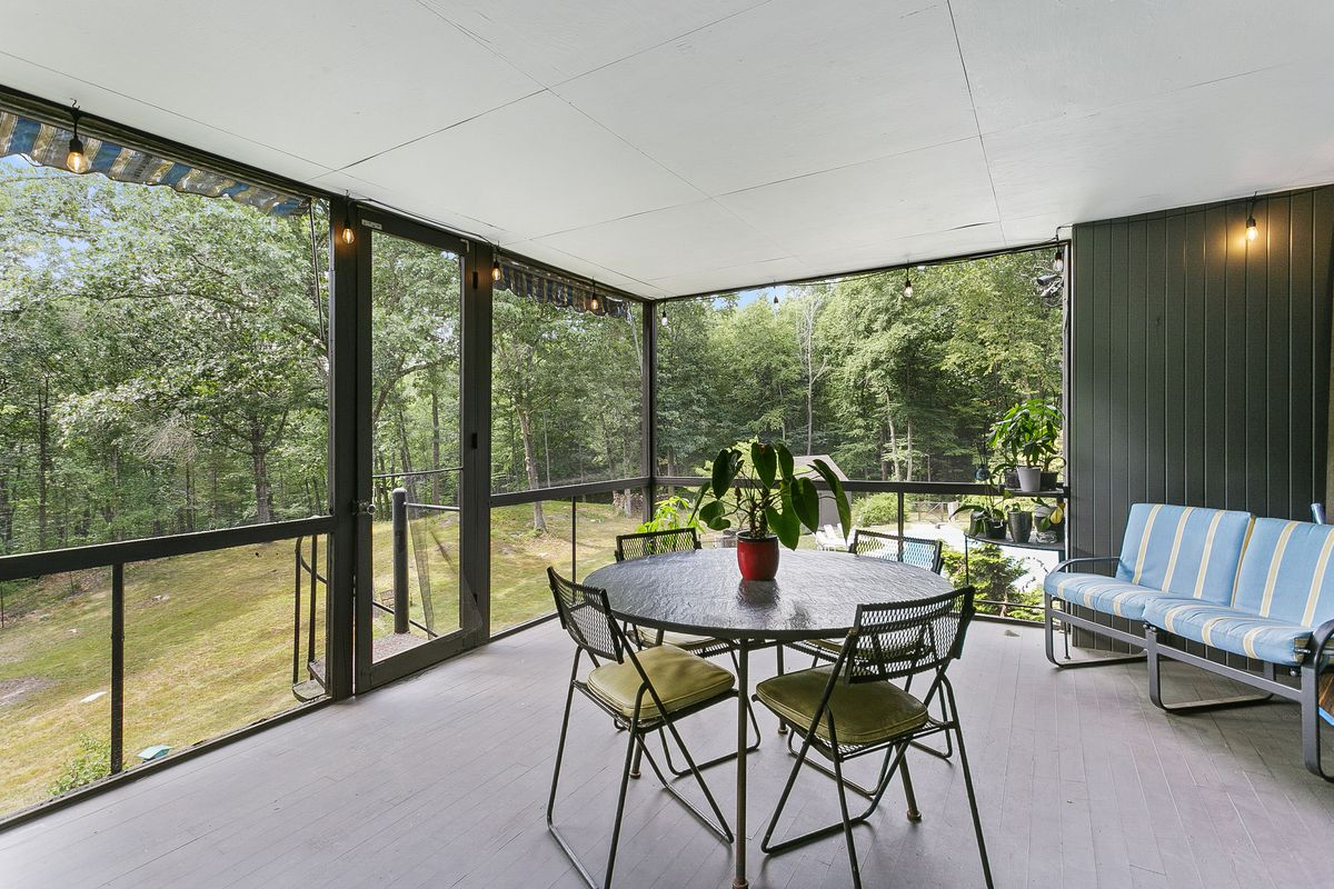 A covered patio has a four-person dining set and a striped couch.