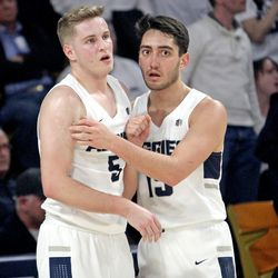 Utah State guard Abel Porter, right, checks on teammate Sam Merrill after Merrill was fouled hard while going to the basket during USU's win over No. 12 Nevada on March 2, 2019.