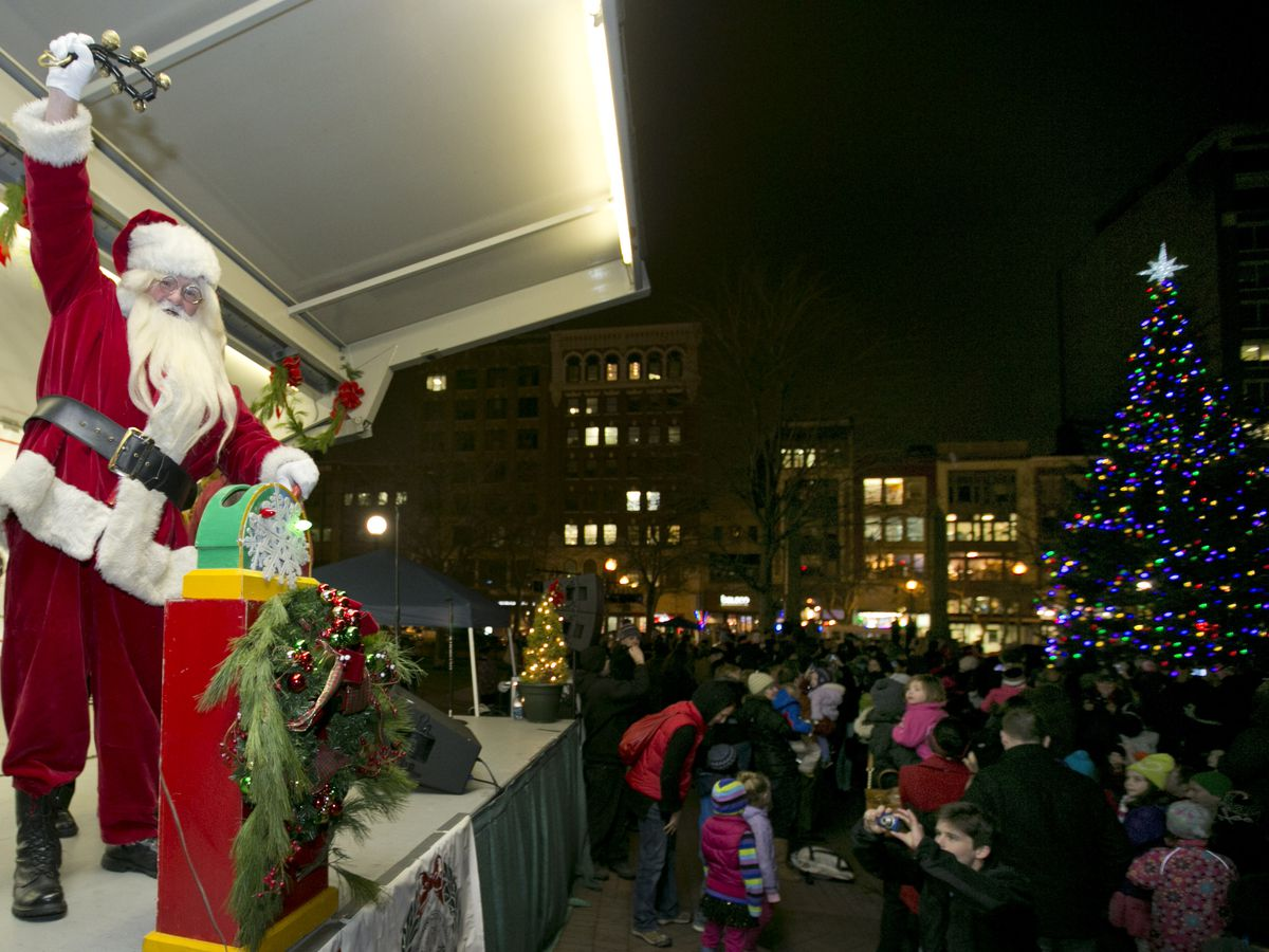 A guy in a Santa Claus suit ringing a bell on a stage as a Christmas tree nearby lights up.
