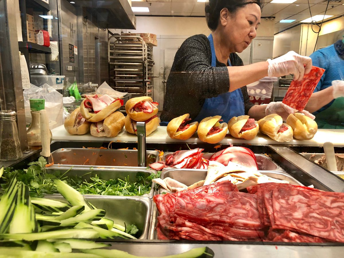 A chef assembles banh mi with meats and veggies