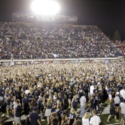 Utah State fans flood the field after the Aggies defeated Utah 27-20 on Friday night.