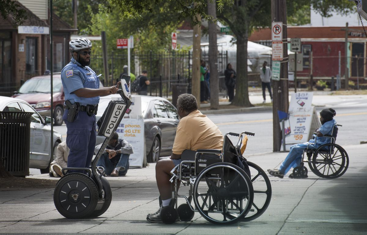 A police officer in Washington, DC talks to a resident while doing his rounds via Segway.