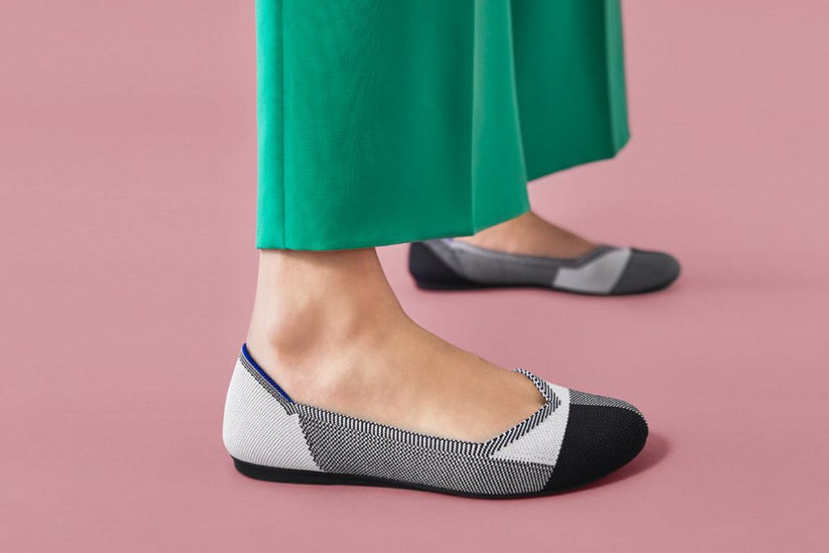 A pair of round-toe flats in black, white, and gray, shown up close on a woman in green pants.