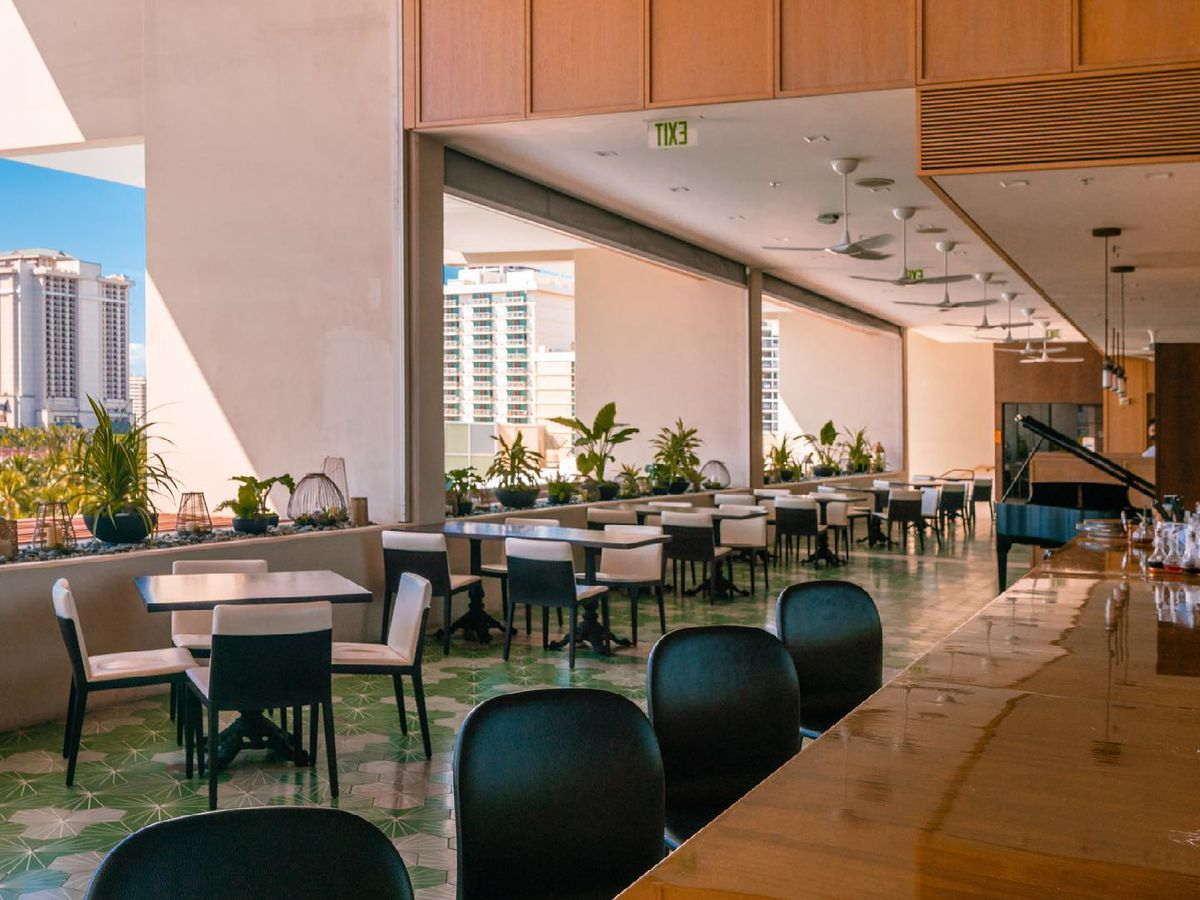 A tall dining space, seen from the bar where empty stools sit, with tables along a far wall with wide open windows