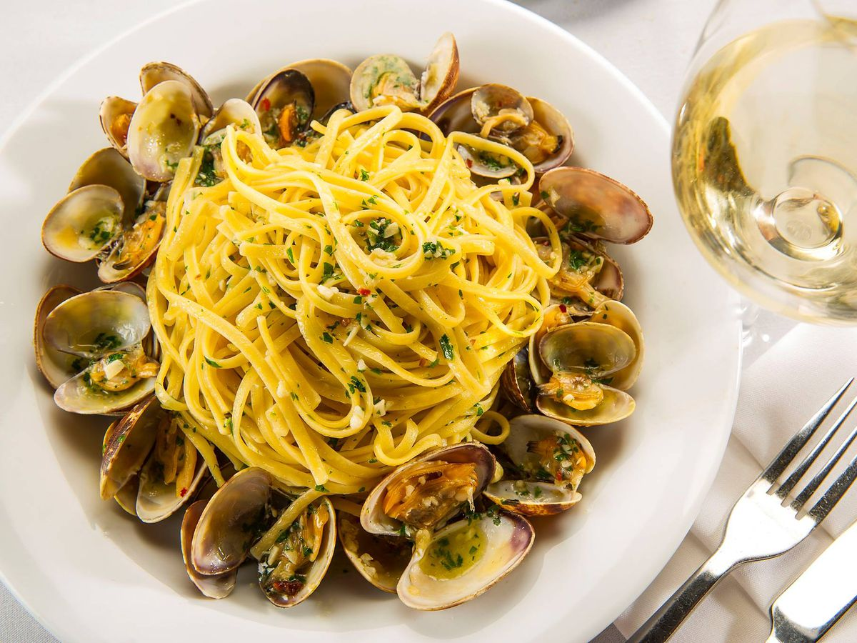 A plate of linguine alle vongole with a glass of wine.