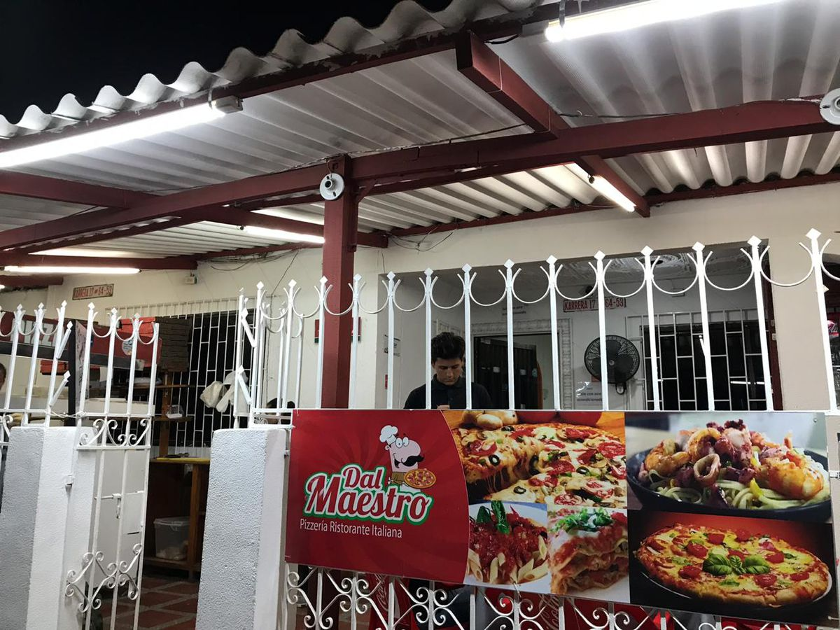 A white iron fence and gate sit in front of a restaurant patio topped with steel covering, with a poster on the fence advertising pizza and other Italian dishes