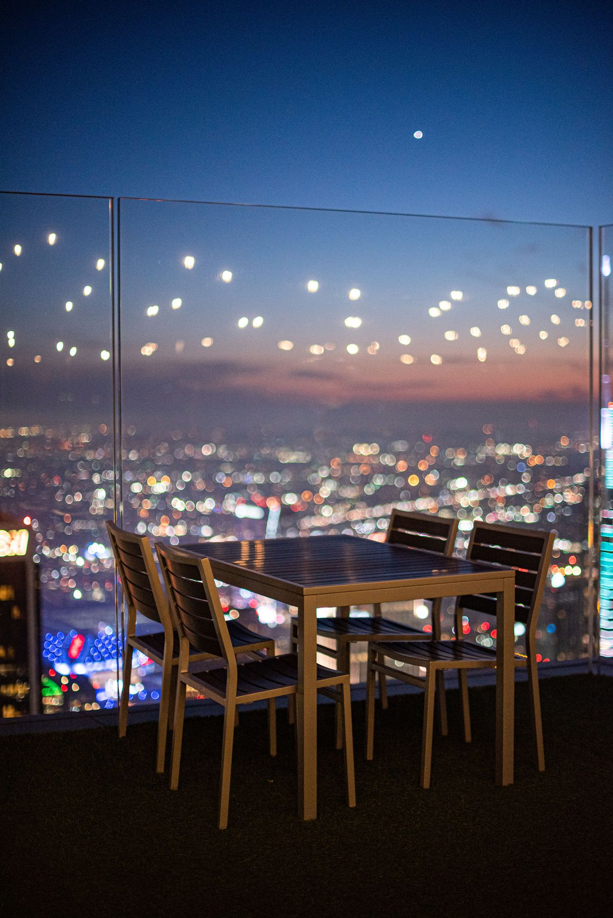 A patio chair on an open air deck overlooking a sparkling city.