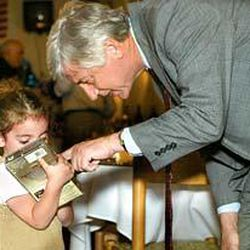 Mayor Rocky Anderson and a young resident examine a Kama Daghlian video at a fund-raiser at Cedars of Lebanon restaurant.