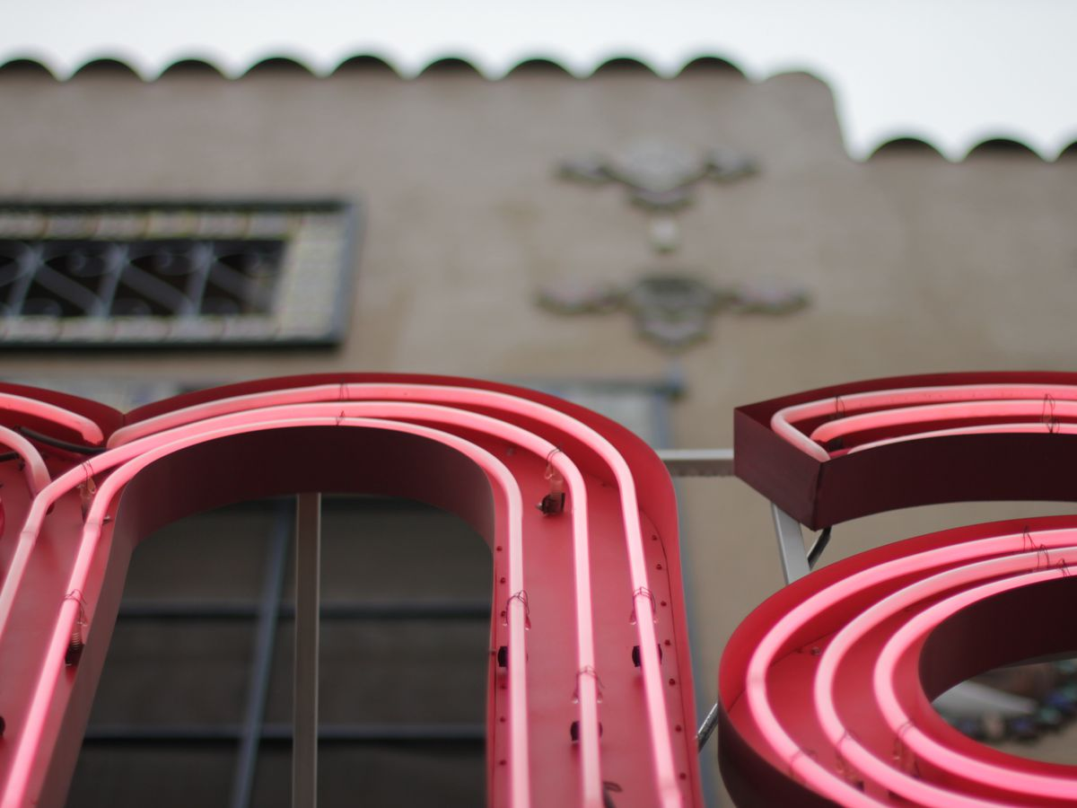 A close-up photo of a neon sign from below. The side of an old brick building and they sky are above.