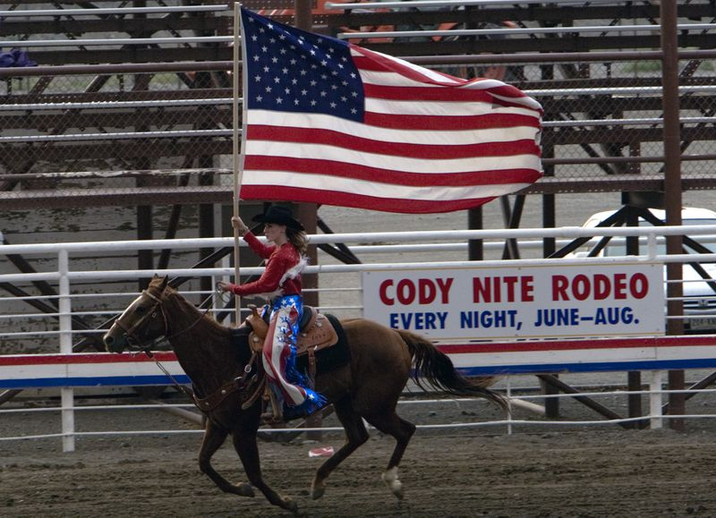 A rider waves the American flag from atop a horse at the Cody Nite Rodeo, Wyoming.