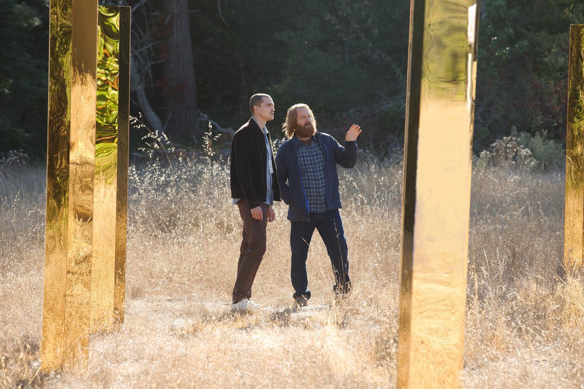Parks and Recreation's Nick Offerman, with long hair and a heavy beard, stands in a pale, grassy field with a forest backdrop, amid tall, reflective golden metal columns. He has a hand up, gesturing toward one of the columns, and appears to be explaining something to a thinner, more clean-cut, younger male associate.