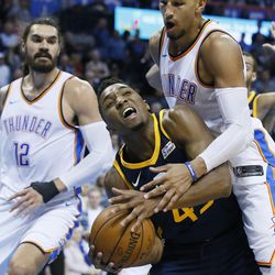 Utah Jazz guard Donovan Mitchell, center, is fouled by Oklahoma City Thunder guard Andre Roberson, right, in the fourth quarter of an NBA basketball game in Oklahoma City, Tuesday, Dec. 5, 2017. Oklahoma City won 100-94. Thunder center Steven Adams (12) is at left. (AP Photo/Sue Ogrocki)